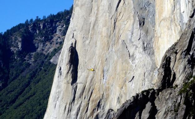 The yellow dot is a helicopter.  about an inch about are two small bumps.  Those are tents (portaledges)  specifically made to dangle off a sheer cliff, so you get a good night's sleep. Since you have at least 5 more days to go...